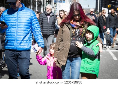 March For Our Lives: A young boy rubs his moms pregnant belly as they walk during the national march to end gun violence, 6th Ave NEW YORK MAR 24 2018.
