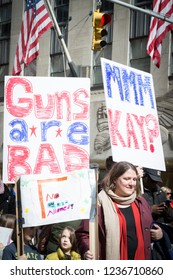 March For Our Lives: A young child looks up as protesters hold signs that says Guns Are Bad and No Guns Allowed at the march on 6th Ave to end gun violence, NEW YORK MAR 24 2018.