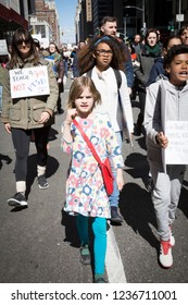 March For Our Lives: A young girl with a raised clenched fist walks with other protesters at the national march to end gun violence, 6th Ave NEW YORK MAR 24 2018.