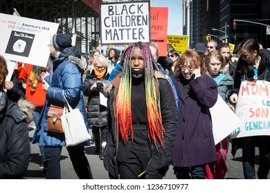 March For Our Lives: A young woman with rainbow braided hair walks with protesters holding signs including one that says Black Children Matter at the march to end gun violence, NEW YORK MAR 24 2018.