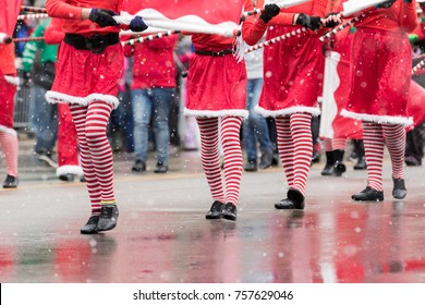 Marchers in a Christmas parade wearing striped tights