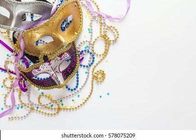Mardi Gras background with masks, beads and copy space. Carnival mask on a white background.