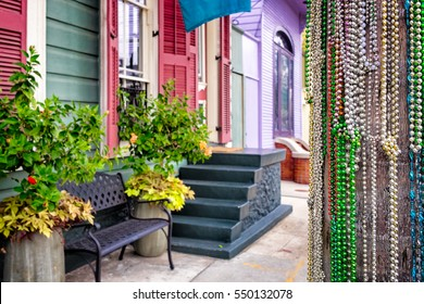 Mardi Gras bead necklaces cover a telephone pole in the foreground of a New Orleans street of colorful shotgun houses. Selective focus on the beads.