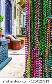 Mardi Gras bead necklaces  in the foreground of a New Orleans street with colorful shotgun houses.