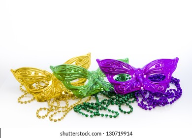 Mardi Gras beads and colorful masks on white backgound.