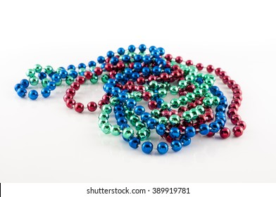 Mardi Gras beads with different colors: red, green and blue isolated on white background