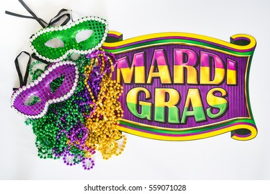 Mardi Gras beads, masks and banner reading  Mardi Gras in traditional festive colors on a white background in horizontal or landscape format