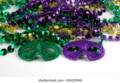 Mardi Gras beads with masks on a white background.