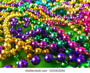 Mardi Gras beads on a green background