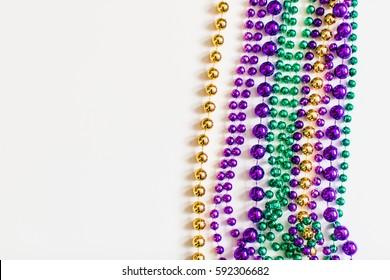 Mardi Gras beads on white background