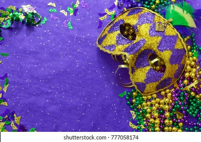 Mardi Gras border or frame of carnival masks, beads, ribbons and confetti in purple, green, gold and black on background of rough textured sparkly paper