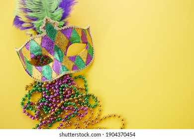 Mardi gras or carnival mask with beads on yellow background. Venetian mask.