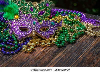 Mardi Gras color beads with masks on wooden table in sunlight - Shutterstock ID 1689425929