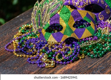 Mardi Gras color beads with masks on wooden table in sunlight - Shutterstock ID 1689425941