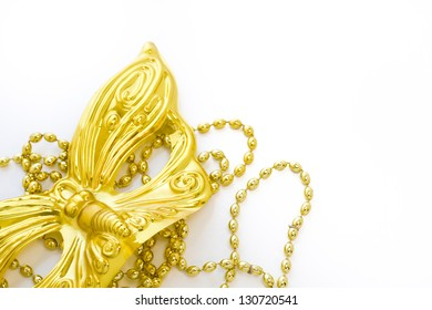 Mardi Gras gold beads and mask on white backgound.