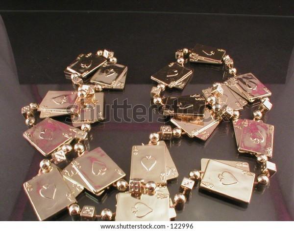 Mardi Gras gold cards necklace on black background.