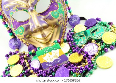 Mardi Gras mask with beads and doubloons at an angle.