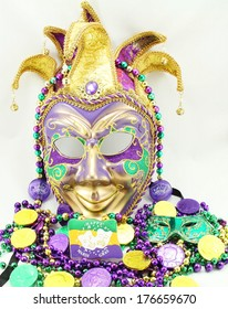 Mardi Gras mask with beads and doubloons.