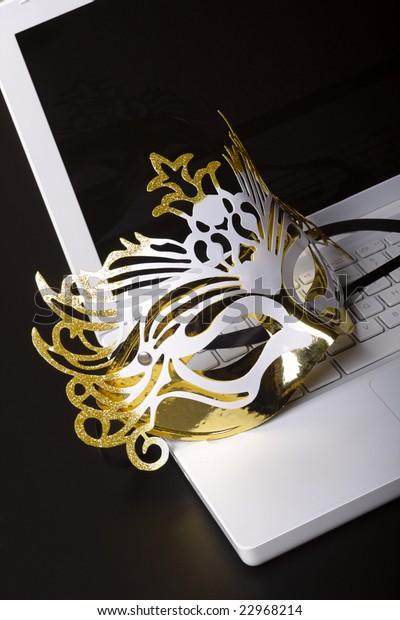 Mardi Gras mask on a white laptop. Close-up on a black-grey background