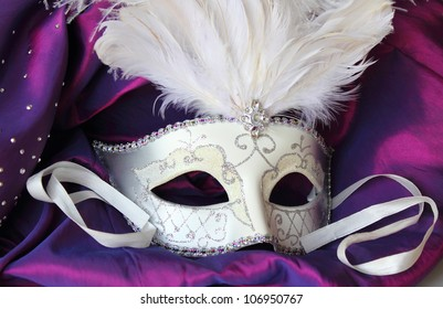 A mardi gras masquerade ball mask on a dress made from purple satin