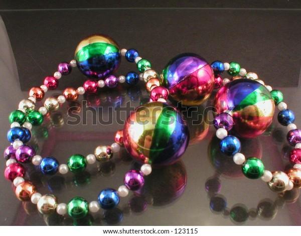 Mardi Gras necklace beadson black background.