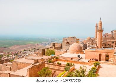 Mardin old town at dusk. Historical orange colored limestone rock buildings