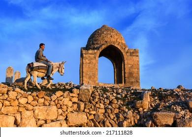 Mardin ,Turkey - 06/02/2014 : Ancient city of Dara in Mardin.Young boy riding donkey.