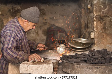 MARDIN, TURKEY - MAY 14, 2014: Elderly man in his workshop plates the copper bowl with tin in Mardin, Turkey.