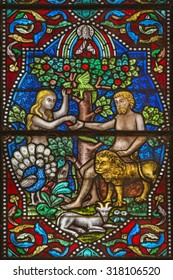 MAREDSOUS, BELGIUM - August 30, 2015: Detail of a an old stained glass window in the abbey of Maredsous (Belgium). Depicted are Adam and Eve in the garden of Eden sharing an apple.