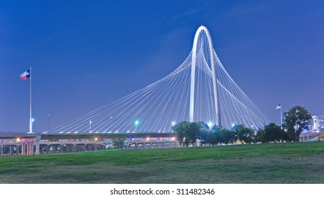 Margaret Hunt Hill Bridge and US flags at night in Dallas, Texas from Trinity Park