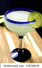 Margarita in a blue rimmed glass with lime on a wooden surface