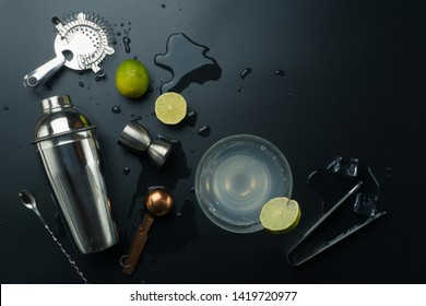 Margarita cocktail and bar equipments, stainless steel cocktail shaker and jigger, copper measuring spoon, bar spoon with strainer, the lemons and ice tongs with ice cubes on the table