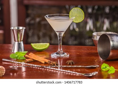 Margarita cocktail, decorated with a slice of lime in a glass on a bar counter surrounded by spices, mint leaves, bar equipment: measuring cup, shaker, bar spoon, masher, tequila.
