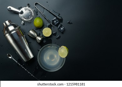 Margarita cocktail glass and bar equipments, stainless steel cocktail shaker and jigger, bar spoon with strainer, the lemons and ice tongs with ice cubes on the table