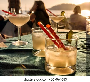 Margarita cocktail glasses on a beach bar table with people, sunset, sea and mountains background