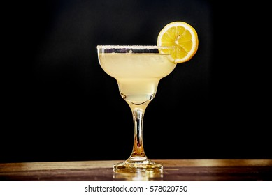 A Margarita Cocktail with a lemon slice on the glass seen in black background.