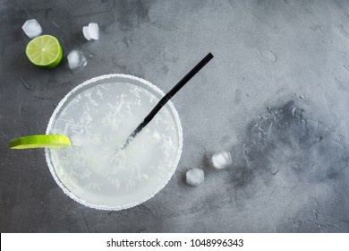 Margarita cocktail with lime and ice on grey concrete background, copy space. Classic Margarita or Daiquiry Cocktail.