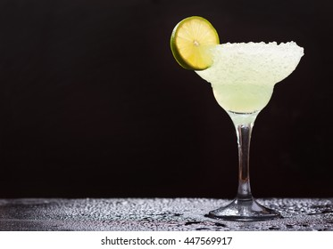 margarita cocktail with lime on dark background