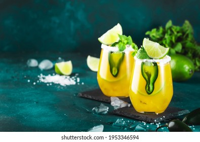 Margarita cocktail with tequila, mango juice, jalapeno pepper, lime and salt, blue background