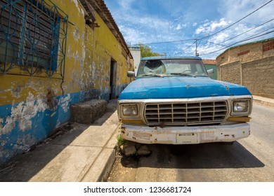 MARGARITA ISLAND, VENEZUELA - APRIL 18/2015: Rusted blue vintage car with smashed window parked in dirty street of Margarita Island against a blue sky.