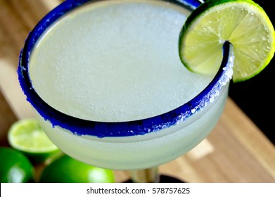 Margarita with lime in a blue rimmed glass on a wood surface