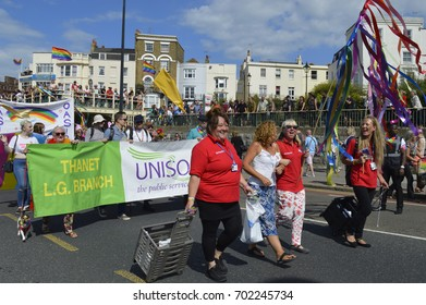 MARGATE, UK-AUGUST 12: Crowds watch people carrying flags and banners marching in the colourful Gay Pride Parade, part of the annual Margate Pride festival. August 12, 2017 in Margate, UK.