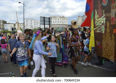 MARGATE,UK-August 6: Children join in the parade with costumed performers taking part in the annual Margate Carnival, watched by crowds lining the street.August 6, 2017 Margate, Kent UK