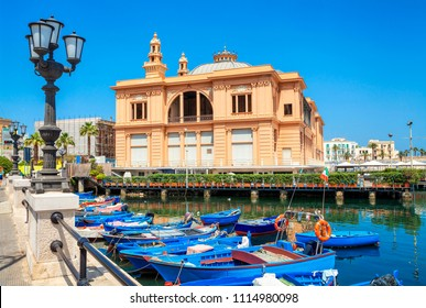 Margherita Theater and fishing row boat in old harbor of Bari, region of Apulia, Italy.