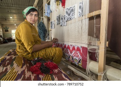 MARGILAN, UZBEKISTAN - MAY 16, 2017: Uzbek woman in local clothes weaves carpet and looks at me, in Margilan, Uzbekistan.