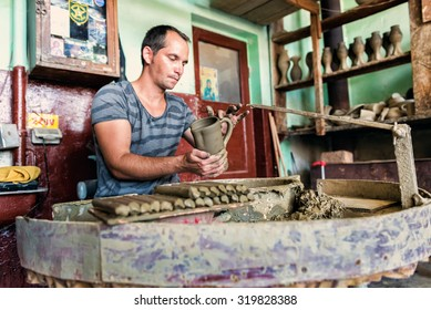 MARGINEA, ROMANIA - AUGUST 08, 2015:  Potter adding handle to a fresh made of clay jug at famous workshop for romanian ceramics from village Marginea .