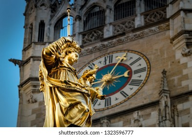 Maria statue with clock of cityhall background. Travel munich bavaria germany