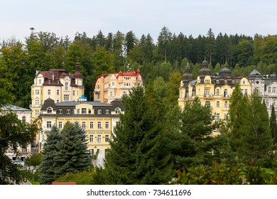 Marianske Lazne, Czech Republic - September 09, 2017: Colorful tenement houses emerge from among the greenery. Many trees give the impression that the city is located in the woodland.
