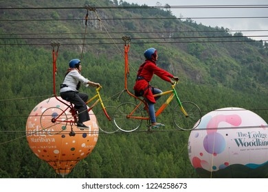 MARIBAYA RESORT ,BANDUNG CITY,INDONESIA. TAKEN ON SEPTEMBER 2018. Unrecognized Asian couple enjoying riding a bike against the sky to glamping wearing safety suit. the famous and adventure activity.