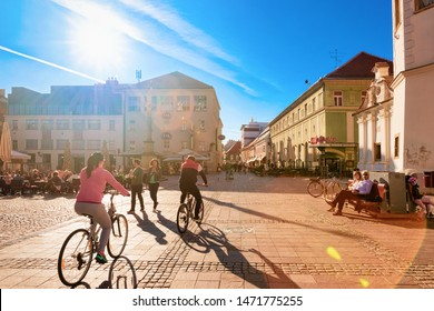 Maribor, Slovenia - March 24, 2019:  People on bicycles on Grajski trg, or Castle Square in Old city in Maribor in Slovenia. Tourists at street cafes and restaurants in Lower Styria in Slovenija.
